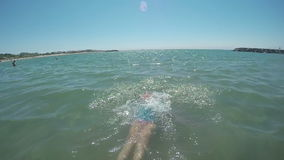 Girl falls back into the sea stock footage