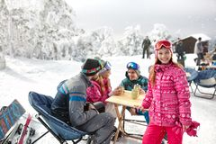 Girl with family in cafe on ski terrain enjoy. Smiling young girl with family in cafe on ski terrain enjoy Royalty Free Stock Photo