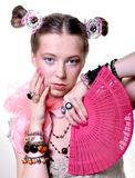 Girl with a fan. A girl, wearing a lot of accessories, holds a fan Royalty Free Stock Photos