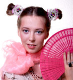 Girl with a fan. Girl, wearing scarf, holds a fan Royalty Free Stock Photo