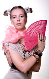 Girl with a fan. A girl, wearing a lot of accessories, holds a fan Royalty Free Stock Image