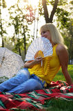 Girl with a Fan. Beautiful girl with a white fan sitting on the mat Stock Photography