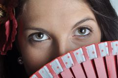 Girl with fan. Eyes of spanish girl with fan and flower in her hair close up Stock Image