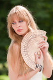 The girl and a fan. The beautiful girl holds a wooden fan Stock Photography