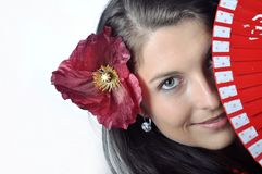 Girl with fan. Face of spanish girl with fan and flower in her hair close up Royalty Free Stock Photos
