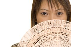 Girl and Fan 5. A pretty young asian girl holds a wooden fan in front of her mouth Royalty Free Stock Photography