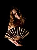 Girl with a fan on black. Stock Photos