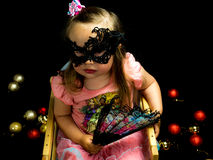 Girl with fan and mask in dress Stock Photography