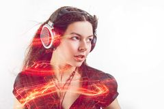 Girl fan sings and dances listening to music. Young brunette woman in big headphones enjoys music stock image