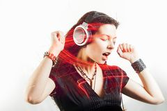 Girl fan sings and dances listening to music. Young brunette woman in big headphones enjoys music royalty free stock photos