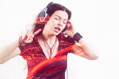 Girl fan sings and dances listening to music. Young brunette woman in big headphones enjoys music royalty free stock photo