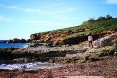 A girl far away on a beach . Stock Photos