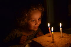 Girl fascinated looking at three burning candles Stock Image