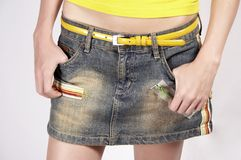Girl in fashion 02. Young girl with jeans skirt, yellow belt and yellow t-shirt royalty free stock image