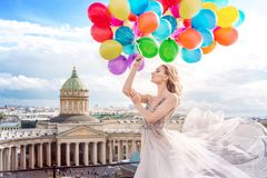 Girl, fashion model with balloons in a waved dress on the background of St. Petersburg, Russia. Kazan Cathedral
