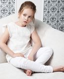 Girl fashion portrait. Child model sitting in chair. White clothes. Cleanliness and innocence Royalty Free Stock Image