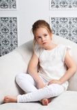 Girl fashion portrait. Child model sitting in chair. White clothes. Cleanliness and innocence Stock Photography