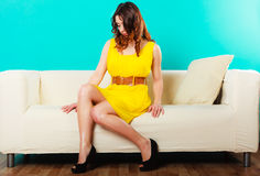 Girl fashionable dress high heels sitting on couch. Stock Photo