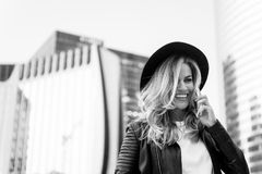 Girl in fashionable leather jacket with cell phone. Beauty look and urban fashion. communication, business and new technology. Fashion model pose smiling Royalty Free Stock Photography