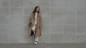 A girl fashionably dressed stands leaning her foot against a concrete wall