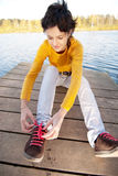 Girl fastens laces on gym shoes Royalty Free Stock Image