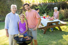 Girl, Father And Grandfather Preparing Barbecue In The Park Stock Photo