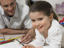 Girl With Father Coloring Book On Floor Royalty Free Stock Photo