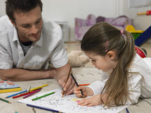 Girl And Father Coloring Book Together On Floor. Little girl and father coloring book together on floor at home Royalty Free Stock Photos