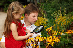 Girl and father, considers plants through loupe Stock Photos