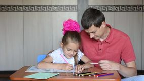 Girl and father first grader solving homework joyfully stock footage