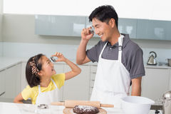 Girl and father holding cookie molds in kitchen Royalty Free Stock Photo