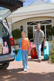 Girl (6-8) and father loading car with luggage, smiling, low angle view Royalty Free Stock Photography