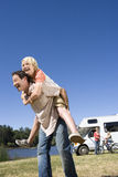 Girl (9-11) on father`s back, mother and brother (10-12) by motor home in background, low angle view Stock Images