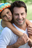 Girl on father's back Stock Images