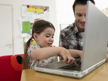 Girl And Father Using Laptop At Table Stock Photos