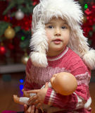 Girl  with a favorite toy doll with Christmas lights Royalty Free Stock Photo