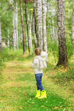 Girl with a favorite toy in the forest on a summer day. back view. Royalty Free Stock Image