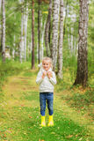 Girl with a favorite toy in the forest on a summer day. Royalty Free Stock Image