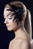 Girl with feathered accessory, she looks down Royalty Free Stock Photos