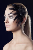 Girl with feathered accessory looks at right Stock Photo