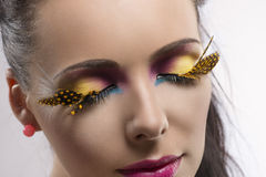 Girl with feathered makeup with closed eyes Royalty Free Stock Photo