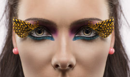 Girl with feathered makeup looks in to the lens Stock Image