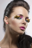 Girl with feathered makeup turned at left Royalty Free Stock Photography