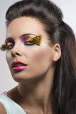 Girl with feathered makeup turned at right Stock Photos