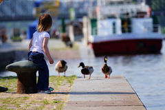 Girl feedind ducks at landing stage. Little beauty girl feedind wild ducks at landing stage or river embankment at sunny day. She is wait for duck. We see ship stock image