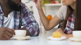 Girl feeding african-american boyfriend with tasty cake, couple drinking coffee stock video