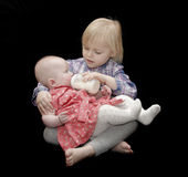 Girl feeding baby girl. Adorable young blond girl feeding her baby sister against a black background Stock Photos