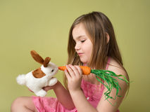 Girl feeding carrots to Easter Bunny Stock Image