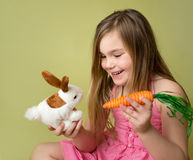 Girl feeding carrots to Easter Bunny Stock Photography