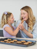 Girl feeding cookie to mother Stock Images